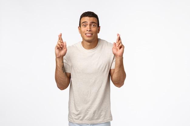 Facet ma nadzieję na stypendium sportowe w piłce nożnej w college'u silny przystojny atletyczny mężczyzna w koszulce, kciuki powodzenia i wyglądający na zmartwionego w oczekiwaniu na ważne wyniki, przewidywanie spełnienia marzeń