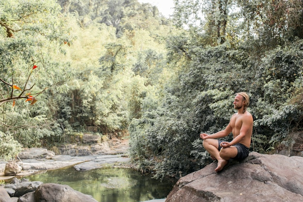 Facet medytuje na kamieniu w lesie