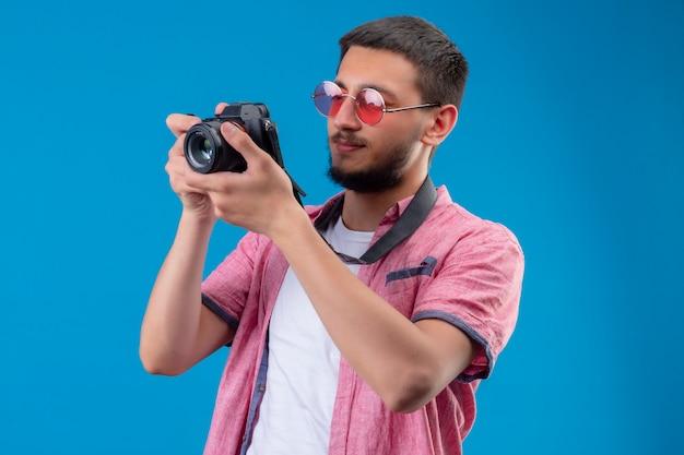 Facet młody przystojny podróżnik w okularach przeciwsłonecznych robi zdjęcie aparatem stojącym na niebieskim tle