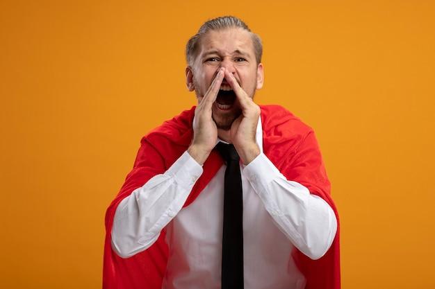 Facet młody superbohater sobie krawat patrząc na kamery dzwoniąc do kogoś na białym tle na pomarańczowym tle
