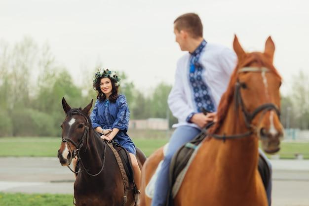 Facet na koniu jadący z przodu, spoglądający przez ramię na swoją dziewczynę, która również jeździ na koniu
