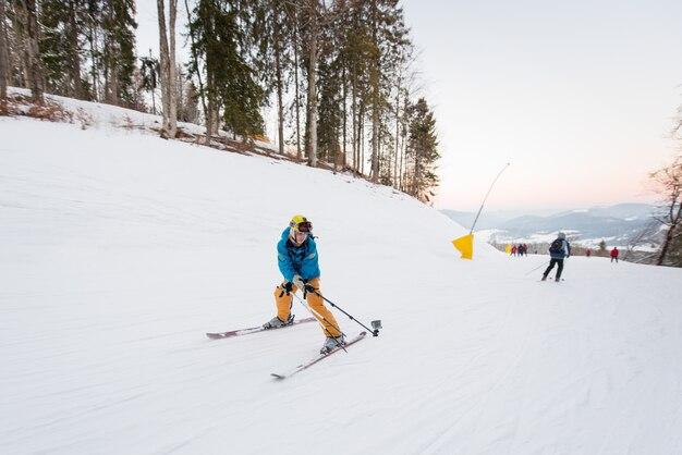 Facet na nartach jedzie po zboczu góry i bierze selfie kijem na zimowy ośrodek