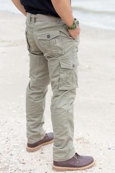 Facet na sobie spodnie cargo i stojąc na plaży
