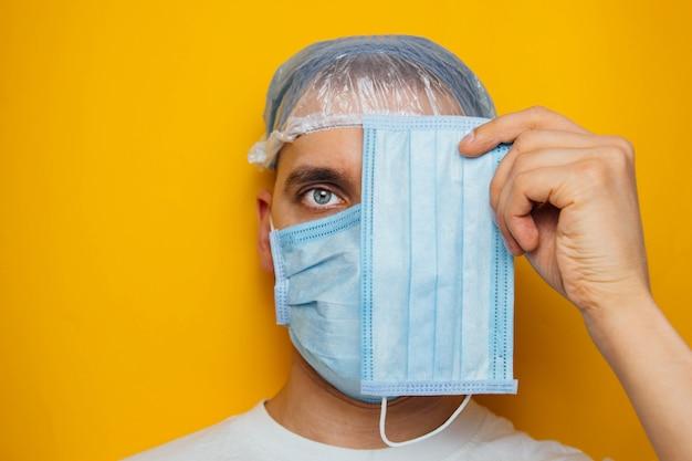 Facet nakłada maskę na oczy. atrakcyjny mężczyzna nakłada maskę i patrzy w kamerę. przeziębienia, grypa, wirus, zapalenie migdałków, ostre infekcje dróg oddechowych, kwarantanna, koncepcja epidemii.