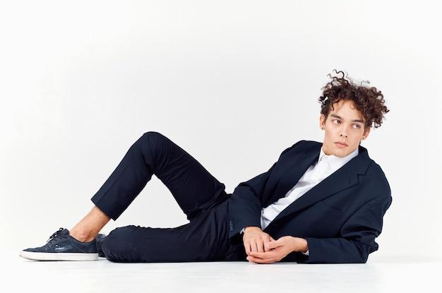 Facet nastolatek w garniturze leży na podłodze i jasne trampki z kręconymi włosami