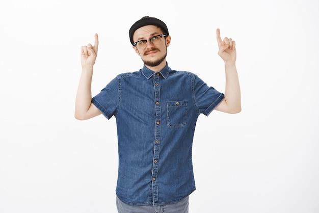 Facet nie jest pod wrażeniem, gdy waha się, czy produkt się uśmiecha i mruży oczy z powodu niepewnych uczuć skierowanych w górę z podniesionymi rękami stojącymi niepewnie i niepewnie w czarnej czapce