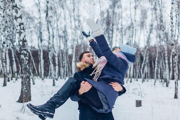 Facet niosący swoją dziewczynę na rękach w zimowym lesie, podczas gdy ona rzuca śniegiem. ludzie bawią się na zewnątrz