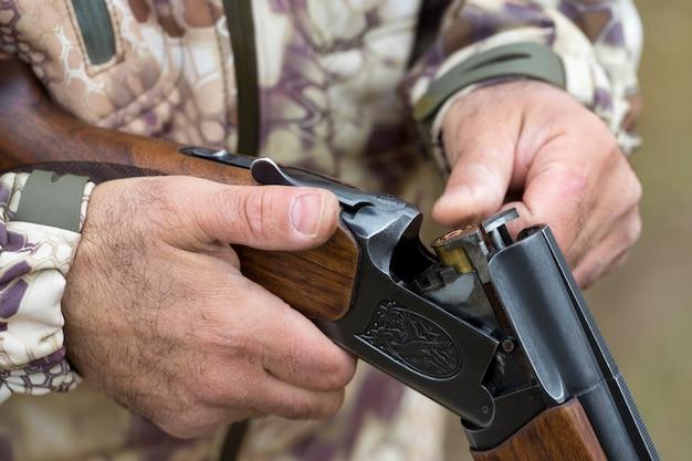Facet odnotowuje wyniki strzałów w tarczę mężczyzna w kamuflażu strzela z nabojów