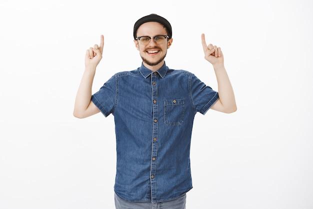 Facet oferujący fajne miejsce do kopiowania, stojący w modnej czarnej czapce i okularach, uśmiechający się radośnie podnosząc ramiona i wskazując w górę, mając dobry nastrój, pozując samotnie