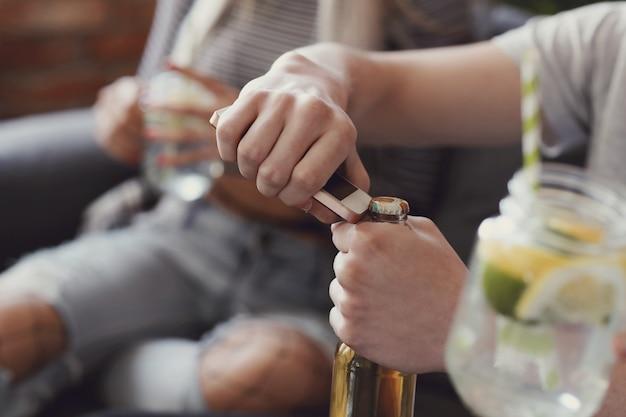 Facet otwierający butelkę piwa
