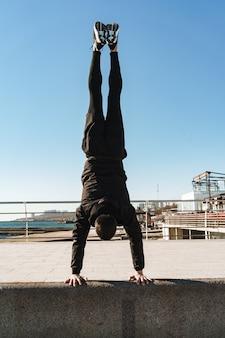 Facet parkour 20s w czarnym dresie robi akrobacje i stoi na ramionach podczas porannego treningu nad morzem