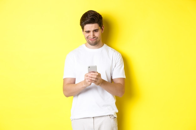 Facet patrzący niezadowolony na ekran smartfona, czytający dziwną wiadomość na telefonie, stojący w białej koszulce na żółtym tle.