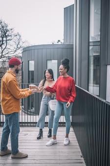 Facet podający kawę dwóm dziewczynom na zewnątrz