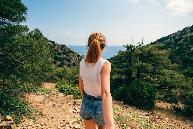 Facet podąża za swoją dziewczyną, trzymając ją za rękę podczas pieszej podróży na świeżym powietrzu w górach