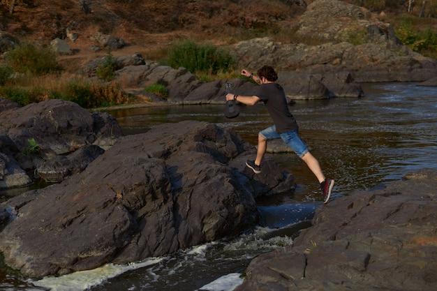 Facet podróżnik przeskakuje przez skały nad górską rzeką, podróżą po rzece i koncepcją ekoturystyki wysokiej jakości p...