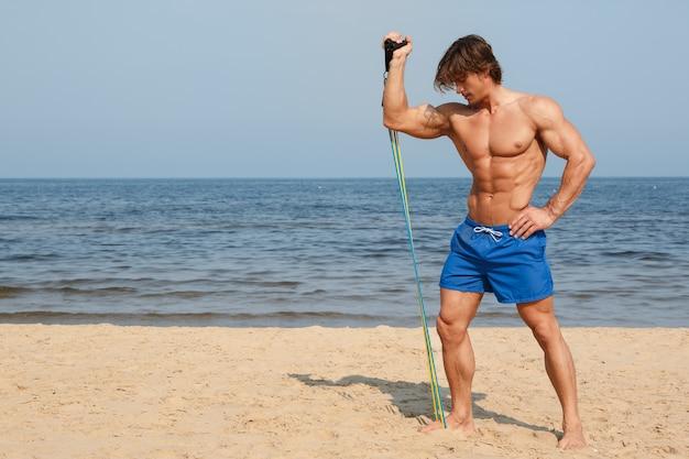 Facet pracujący z gumką na plaży