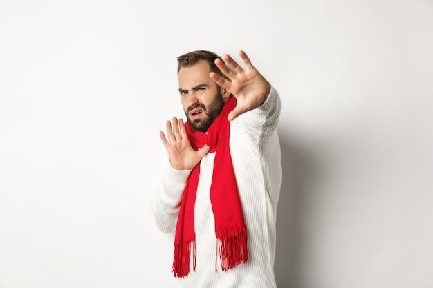 Facet proszący o zatrzymanie się, krzywiący się i odsuwający się od aparatu, zakrywający twarz rękami, stojący na białym tle w czerwonym szaliku i swetrze