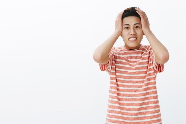 Facet przyciskający dłonie do głowy i zaciskający zęby, jest niespokojny i zaniepokojony, że ma kłopoty z zapominaniem o wykonaniu ważnego zadania na czas