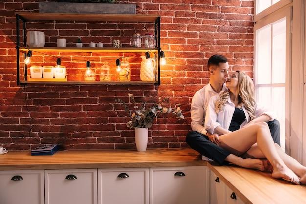 Facet przytula dziewczynę i chcą się całować. para siedzi w kuchni przy oknie. razem w domu.