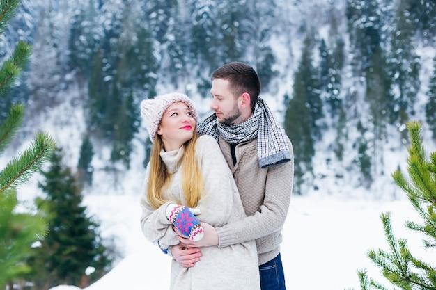 Facet przytula dziewczynę od tyłu i patrzą na siebie w górzystym zimowym lesie