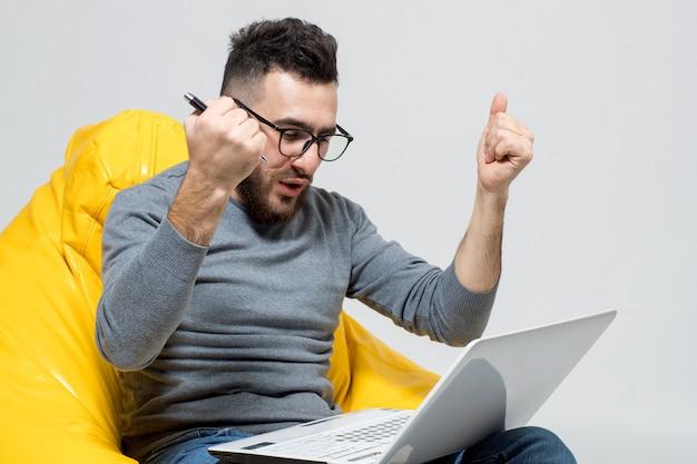 Facet raduje się podczas pracy na laptopie