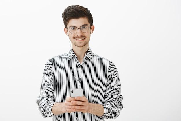Facet robi notatki podczas słuchania audiobooka. portret przyjazny atrakcyjny kaukaski mężczyzna z wąsem i brodą, nosząc słuchawki, oglądając wspaniały film w smartfonie, uśmiechając się