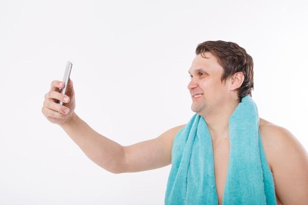 Facet robi selfie po porannych zabiegach. mężczyzna patrzy w aparat w telefonie. gładko wygolona twarz. niebieski ręcznik na szyi. człowiek i nowoczesne technologie. rozmowa za pośrednictwem łącza wideo