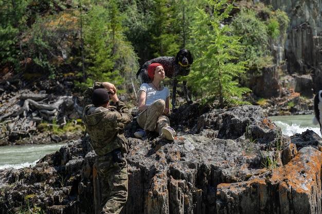 Facet robi zdjęcia swojej dziewczynie na tle górskiego krajobrazu. sesja zdjęciowa w lesie z psem