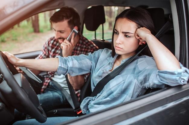 Facet rozmawia przez telefon i śmieje się, gdy dziewczyna prowadzi samochód