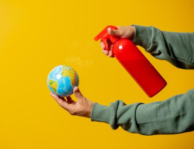 Facet rozpyla środek dezynfekujący na kuli ziemskiej na żółto