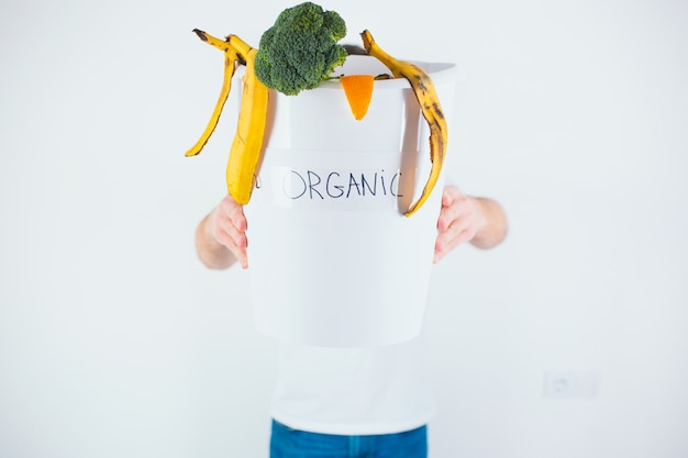 Facet sam trzyma wiadro z odpadami organicznymi