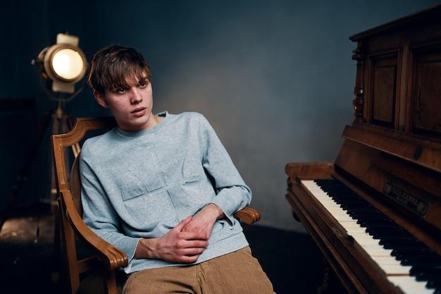 Facet siedzący na krześle obok fortepianu pozujący zdjęcie
