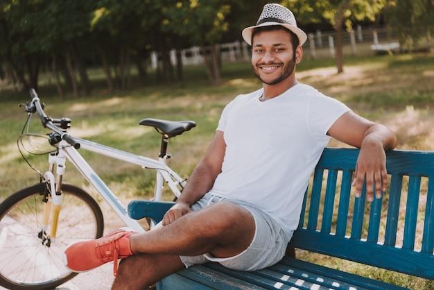 Facet siedzi na ławce w parku obok roweru.