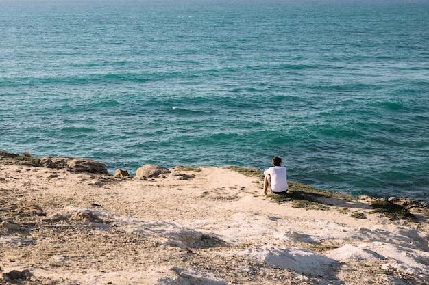 Facet siedzi na plaży przy klifie