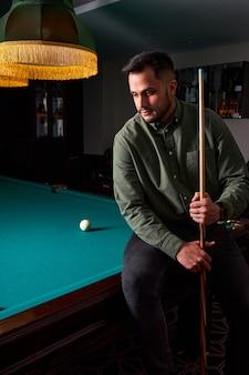 Facet siedzi przygnębiony po złej grze w bilard, przegrany ma nieudaną grę w snookera. portret