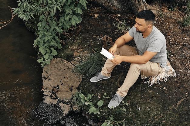 Facet siedzi w miejskim parku i cieszy się naturą