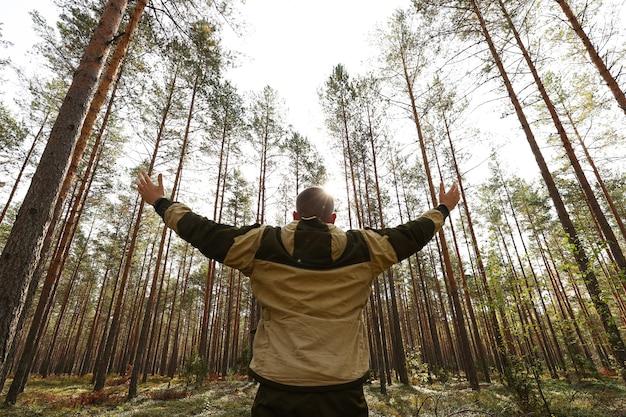 Facet spaceruje po lesie w słoneczny dzień