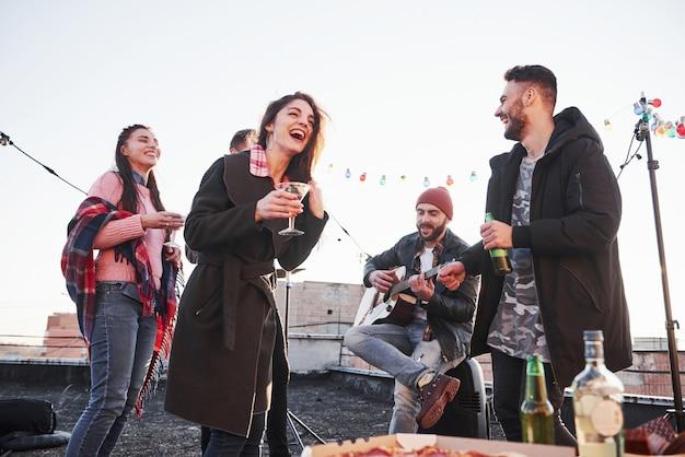Facet śpiewa zabawną piosenkę. rozochoceni młodzi ludzie ono uśmiecha się i pije przy dachem. pizza i alkohol na stole. gitarzysta