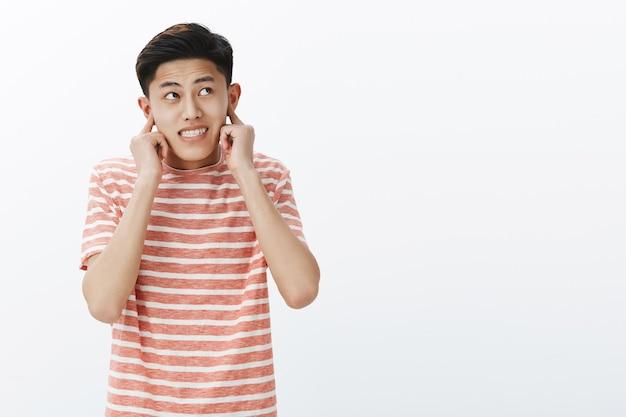 Facet spodziewający się głośnego hałasu, zamykając uszy palcami wskazującymi, zaciskając zęby i patrząc podekscytowany w prawy górny róg