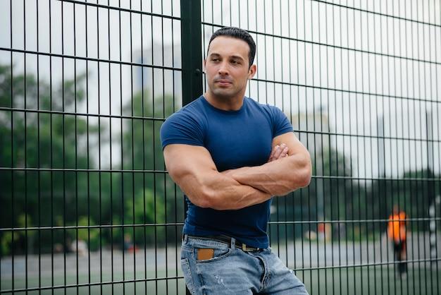 Facet sportowy stoi w pobliżu boiska sportowego.