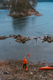 Facet stoi nad zamarzniętym jeziorem z wiosłem