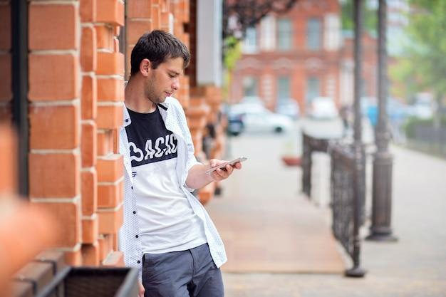 Facet stoi przy ścianie z czerwonej cegły budynku i patrzy przez telefon
