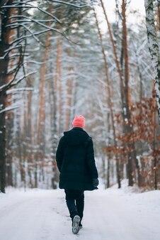Facet stojący na drodze w środku lasu otoczony śniegiem