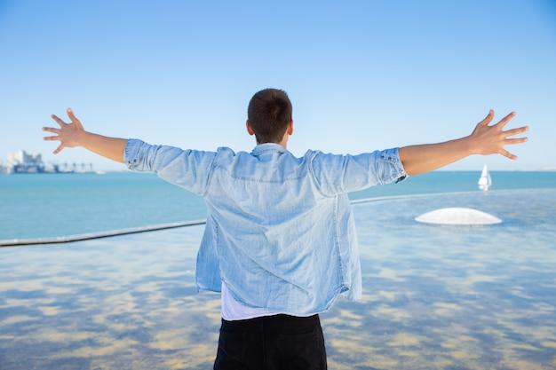Facet stojący na morzu i rozkładający ręce