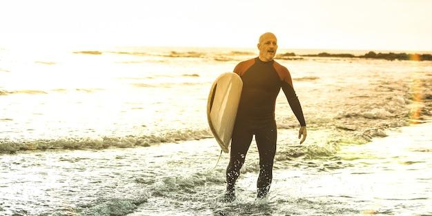 Facet surfer chodzący z deską surfingową o zachodzie słońca na teneryfie - trener surfowania na długich deskach w akcji - koncepcja podróży sportowej z miękkim skupieniem dzięki podświetleniu - ciepłe, słoneczne odcienie filtrowane
