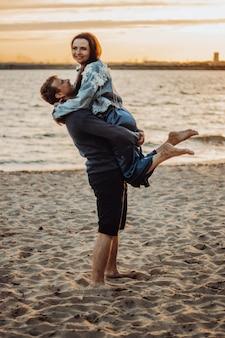 Facet trzyma dziewczynę w ramionach na plaży. letnia romantyczna randka o zachodzie słońca.