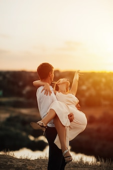 Facet trzyma dziewczynę w ramionach.
