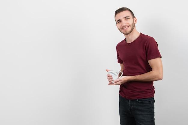 Facet trzyma filiżankę kawy i uśmiech