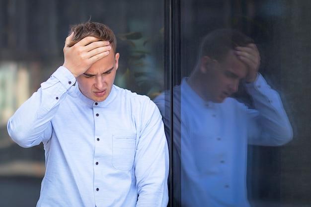 Facet trzyma głowę formalnie ubraną w białą koszulę. ból głowy lub gorączka u mężczyzny.