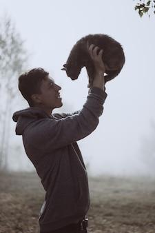 Facet trzyma kota w parku. park jest spowity mgłą